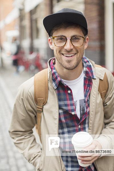 Mann mit Tasse Kaffee auf der Stadtstraße