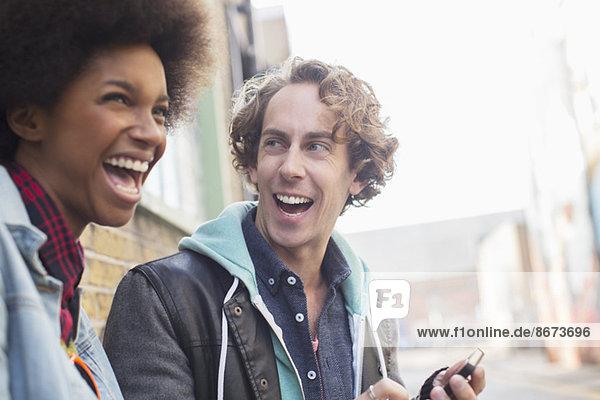 Pärchen lachen zusammen auf der Stadtstraße