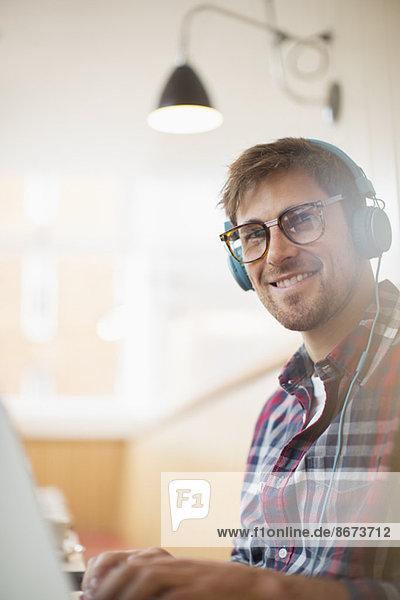 Mann mit Kopfhörer und Laptop