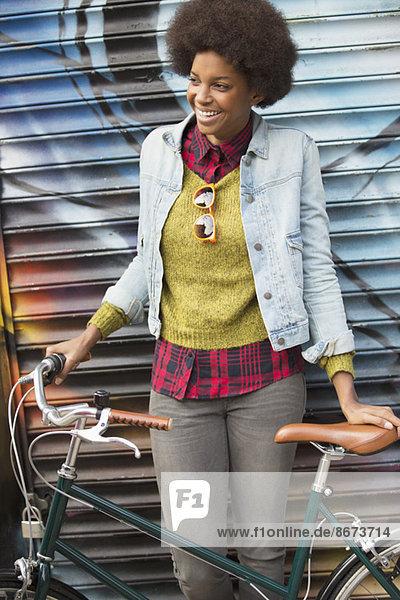 Frau hält Fahrrad vor Graffiti-Wand