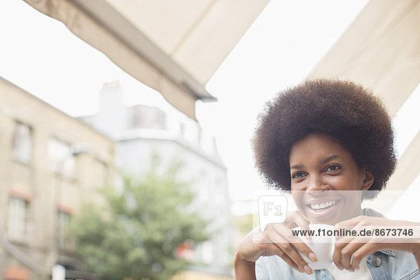 Frau trinkt Kaffee im Straßencafé