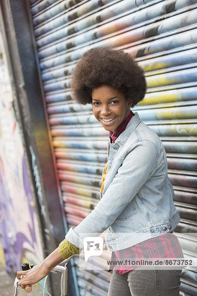 Frau mit Fahrrad vor der Graffiti-Wand