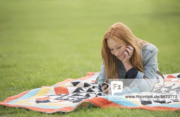 Frau mit Handy auf Decke im Park