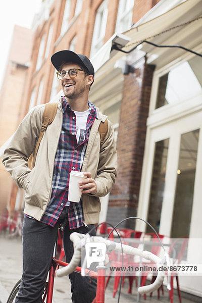 Mann trinkt Kaffee auf dem Fahrrad auf der Stadtstraße