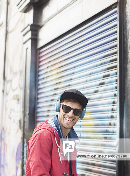 Mann hört Kopfhörer in der Nähe der Graffiti-Wand