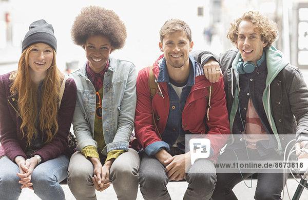 Freunde lächeln auf der Stadtbank