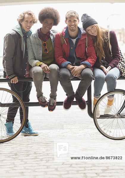 Freunde lächeln zusammen auf dem Fahrradträger.
