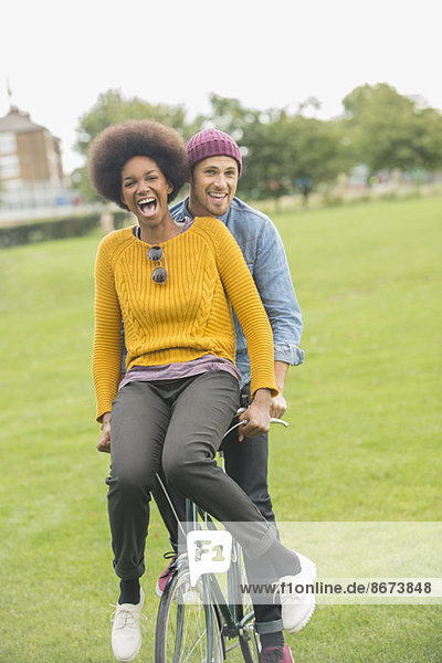 Couple riding bicycle together in park