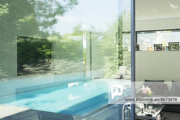Schwimmbad spiegelt sich in den Glasfenstern des modernen Hauses wieder