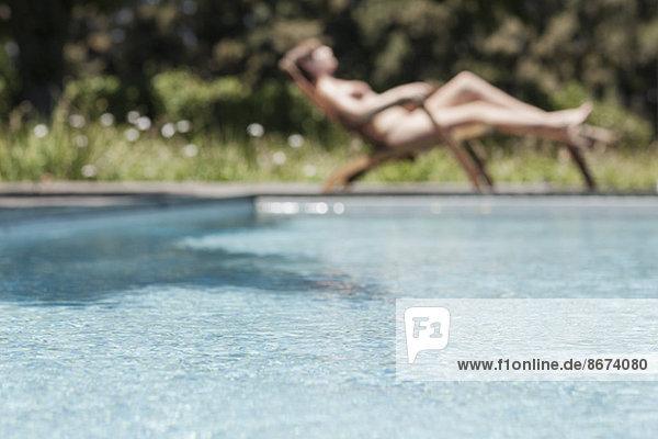 Frau beim Sonnenbaden am Schwimmbad