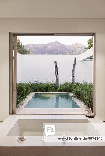 Modernes Badezimmer mit Blick auf Schwimmbad und Berge