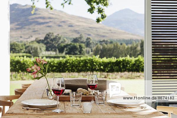 Esstisch und Stühle auf einer luxuriösen Terrasse mit Blick auf den Weinberg