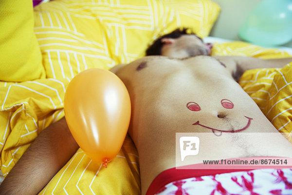 Mann mit Smiley-Gesicht auf dem Bauch schlafend nach der Party
