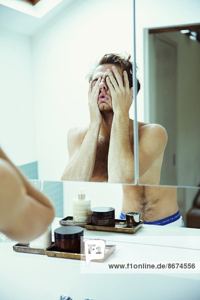 Hungover Mann bedeckt Gesicht am Spiegel