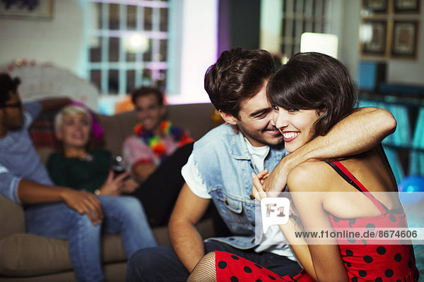 Couple hugging in living room at party