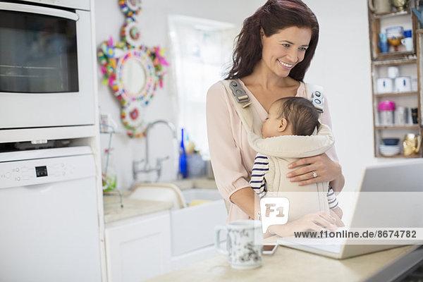 Mutter hält Baby Junge und mit Laptop in der heimischen Küche