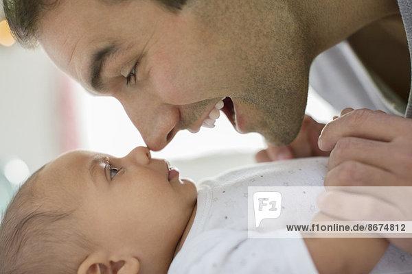 Vater reibt sich die Nase mit dem Jungen.