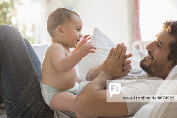 Vater spielt mit dem kleinen Jungen im Bett