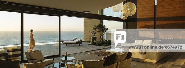 Frau auf der modernen Terrasse mit Blick auf den Ozean