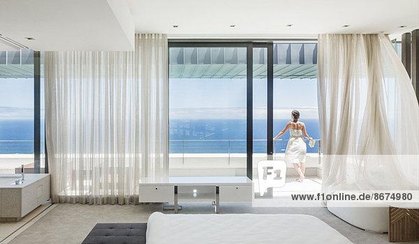 Frau auf modernem Balkon mit Meerblick
