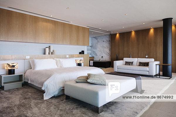 Bett und Sofa im modernen Schlafzimmer