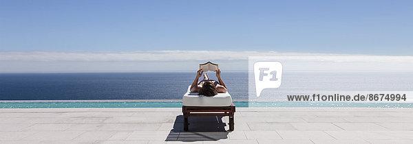 Frau entspannt sich auf einem Liegestuhl am Pool mit Blick aufs Meer