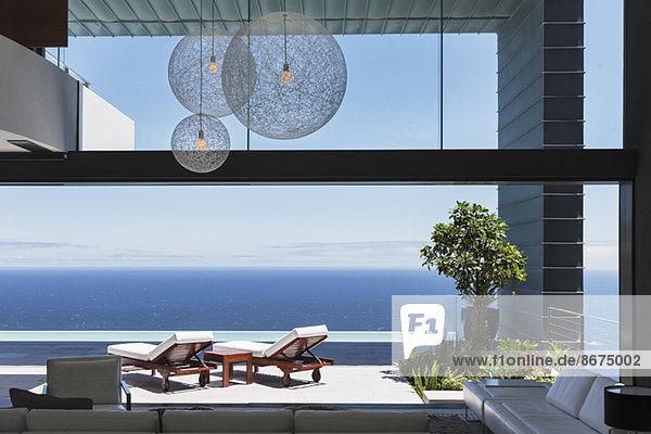 Liegestühle auf dem Balkon mit Blick auf das Meer
