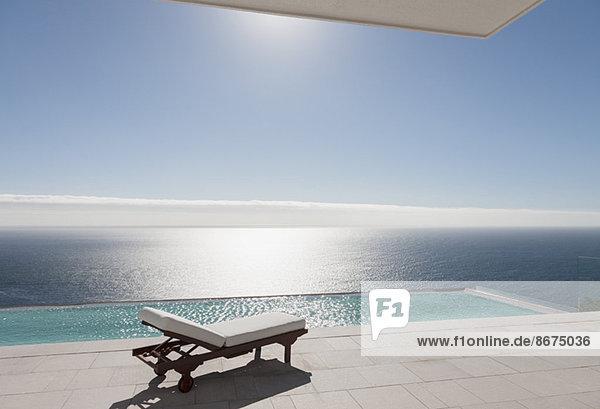 Sessel und Infinity-Pool mit Blick auf das Meer