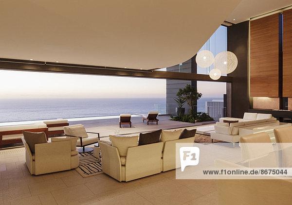 Wohnzimmer im modernen Haus mit Blick auf das Meer bei Sonnenuntergang