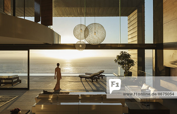 Frau im modernen Haus mit Meerblick