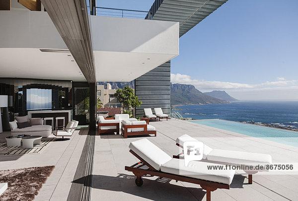Moderne Terrasse und Infinity-Pool mit Blick auf den Ozean