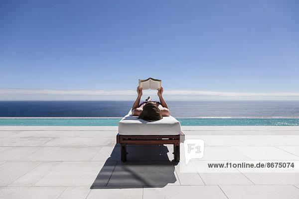 Frau liest auf Liegestuhl am Pool mit Blick auf den Ozean