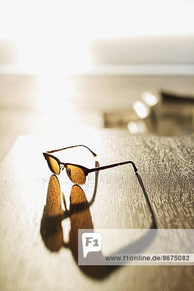 Sonnenbrille mit Schatten auf dem Tisch