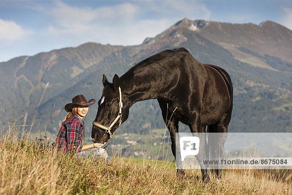 Junge Frau mit Hannoveraner  Rappe  auf Bergwiese im Herbst  Nordtirol  Österreich