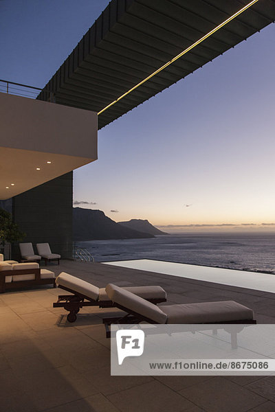 Balcony of modern house overlooking ocean at sunset