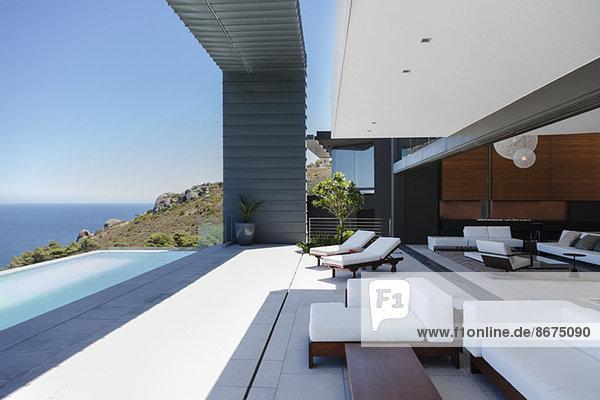 Liegestühle und Infinity-Pool auf der modernen Terrasse mit Blick auf das Meer
