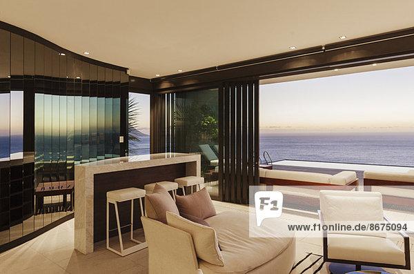 Modernes Wohnzimmer und Bar mit Blick auf das Meer bei Sonnenuntergang