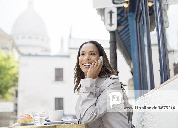 Businesswoman on cell phone at sidewalk cafe near Sacre Coeur Basilica  Paris  France