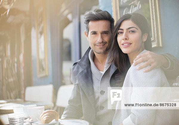 Couple sitting together at sidewalk cafe