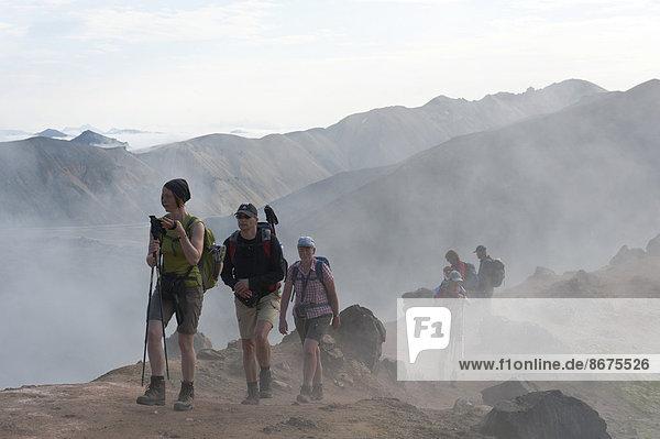 Trekking in Berglandschaft  Wandergruppe geht durch Nebel  Solfataren-Dampf  Brennisteinsalda  Landmannalaugar  Rangárþing ytra  Suðurland  Island  Skandinavien