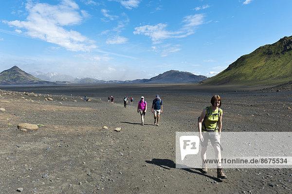 Trekking im Hochland  Wanderer gehen über vegetationslose Schotterfläche  Trekkingweg Laugavegur  hinten links Berg Storasula  Utigönguhöfðar bei Emstrur  Rangárþing ytra  Suðurland  Island  Skandinavien