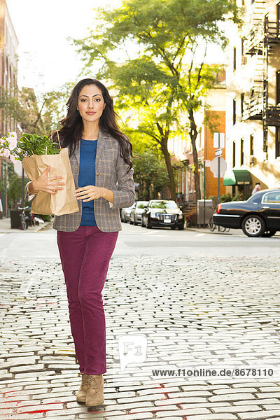 Mixed race woman carrying shopping bag on urban street