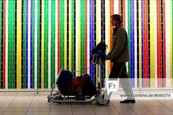 Man pusching a trolley with luggage  passing by a wall with colorful tiles  Johannesburg  South Africa  Africa.