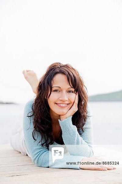 liegend  liegen  liegt  liegendes  liegender  liegende  daliegen  Frau  lächeln  Küste  Kai  braunhaarig  Blick in die Kamera  hübsch