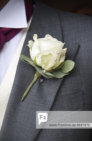 Ein Bräutigam in grauer Jacke und weißem Hemd  mit einer weißen Rosenboutonniere im Knopfloch.