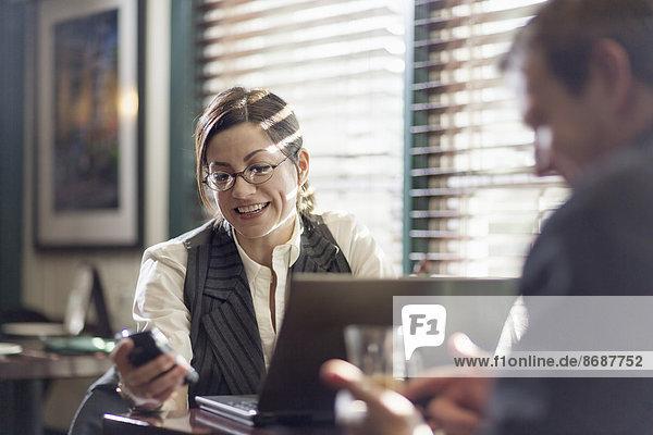 Eine Frau und ein Mann  die an Schreibtischen sitzen und arbeiten. Beide benutzen Smartphones.