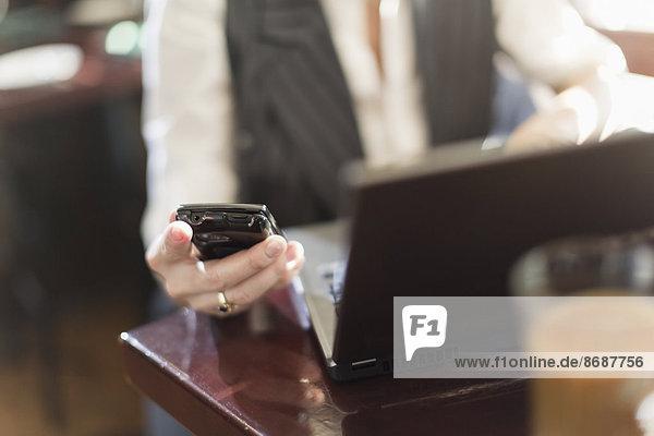 Eine Frau sitzt an einem Schreibtisch und hält ein Smartphone mit einem Laptop-Computer in der Hand.