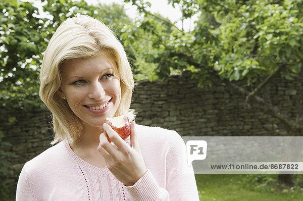 junge Frau junge Frauen halten Apfel gegessen Hälfte