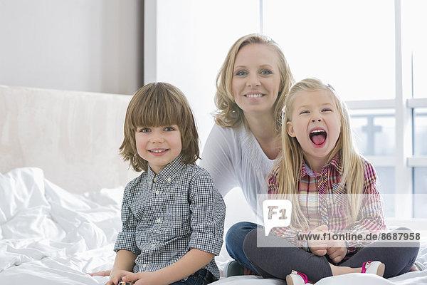 Portrait of happy mother with children in bedroom