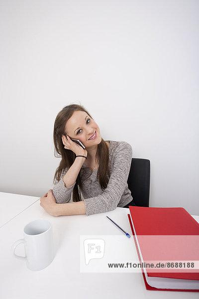 benutzen  Portrait  Geschäftsfrau  Schreibtisch  Schönheit  Telefon  Büro  Handy